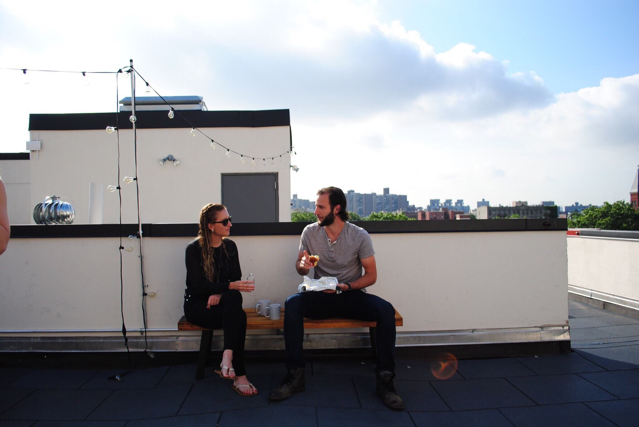 Two members enjoy breakfast on the rooftop on Common Havemeyer in Williamsburg.