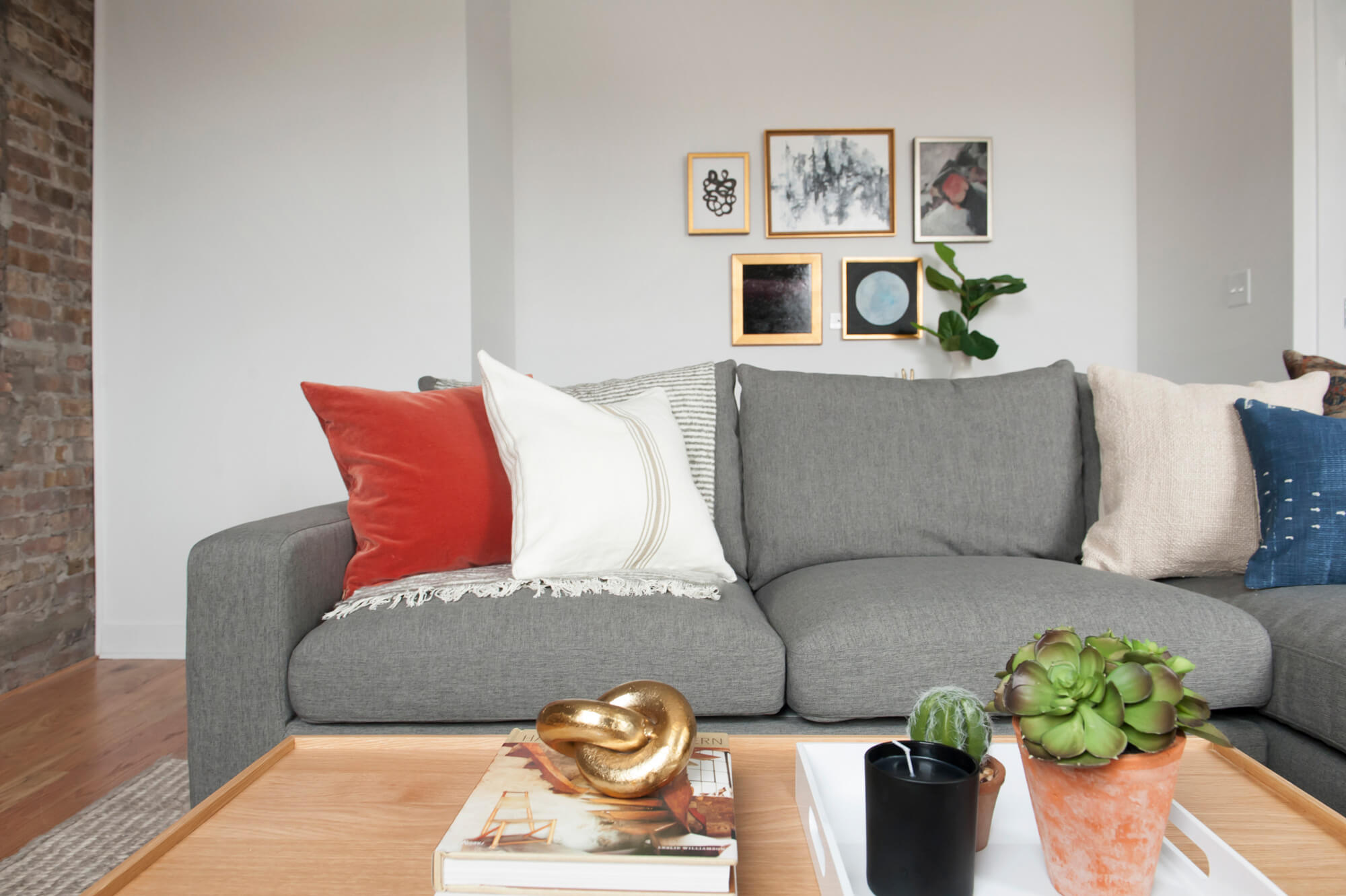 The perfect pop of terra-cotta in the picture, pillow, and plant pot.